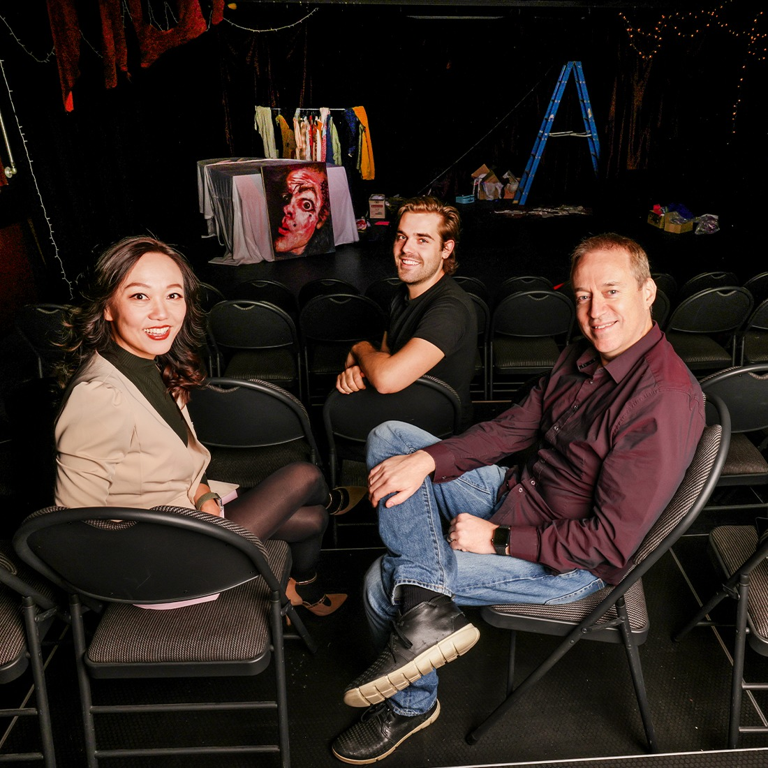 Three people sitting in chairs in a theatre facing the camera