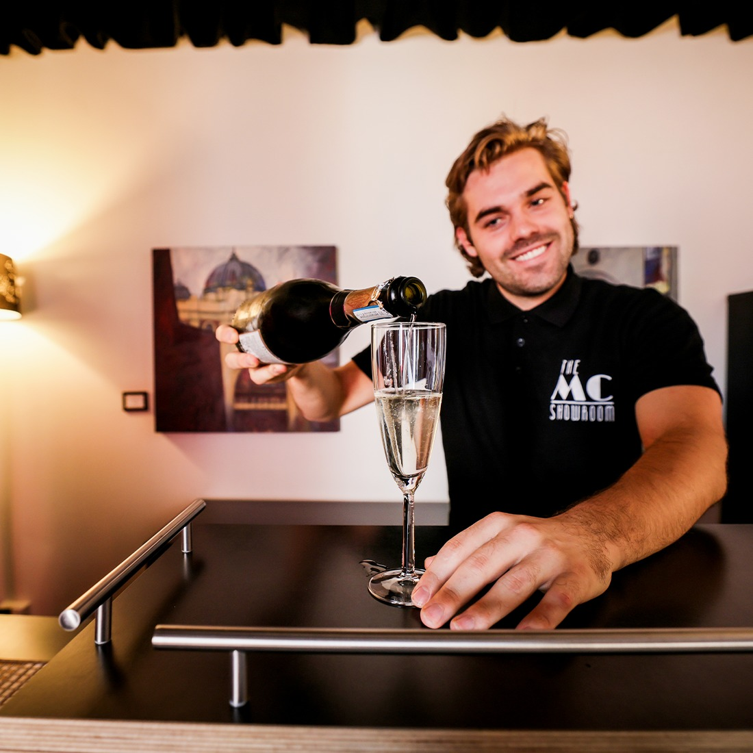 A man at a bar, pouring a glass of champagne