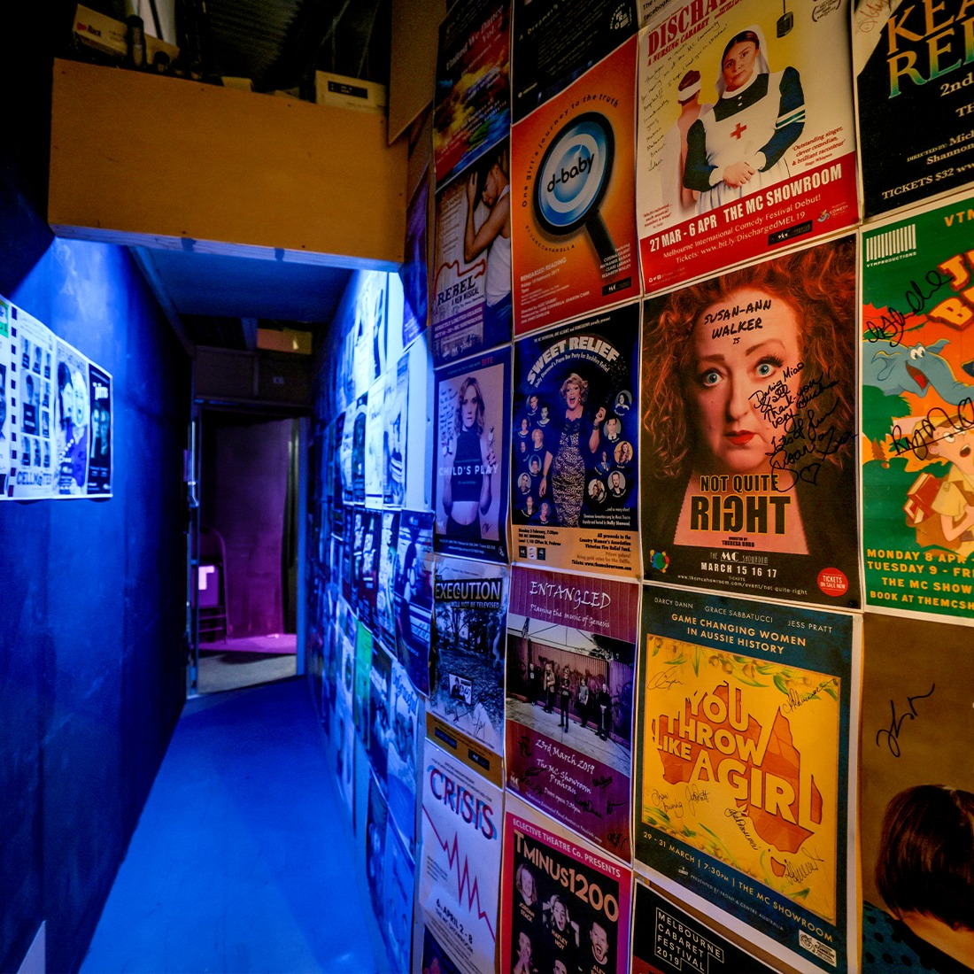 A hallway decorated with theatre posters