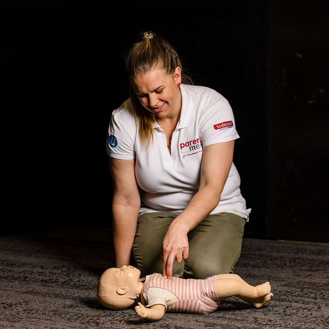 Woman kneeling on the ground, showcasing how to give a baby compressions