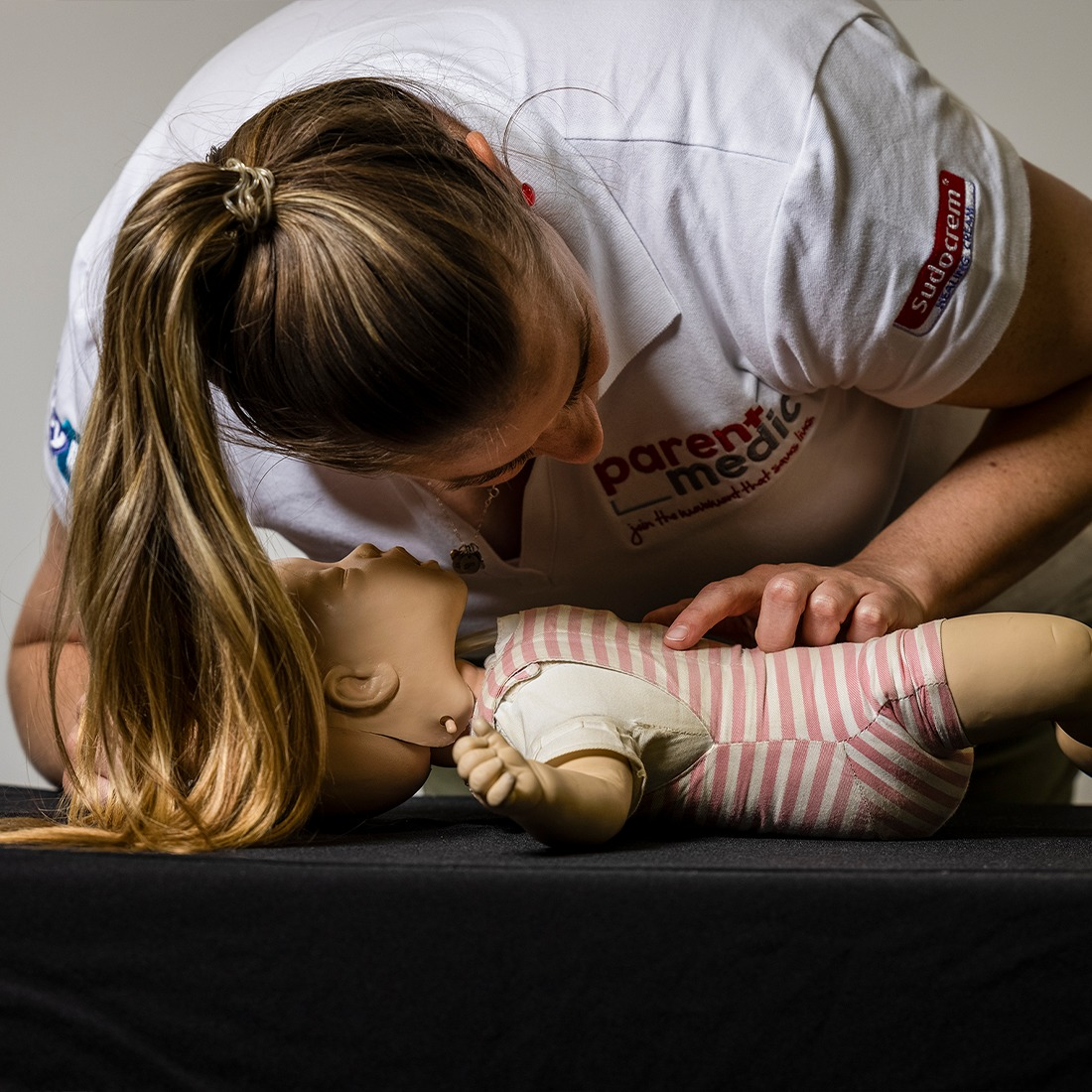 Women leaning over a baby doll showing how to listen for a childs breath if they are unwell