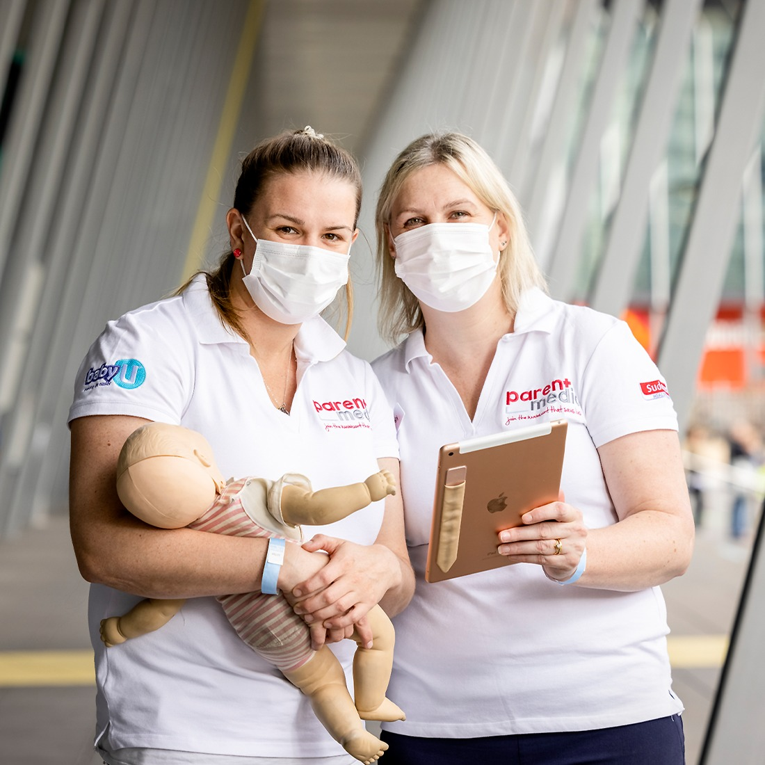Two woman from parentmedic, holding a CPR doll and a clipboard