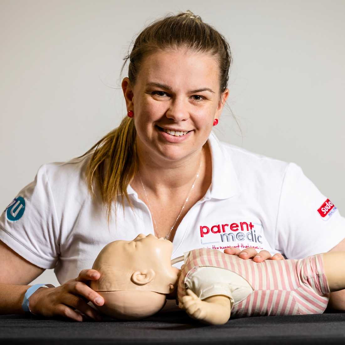 Woman kneeling over a CPR baby