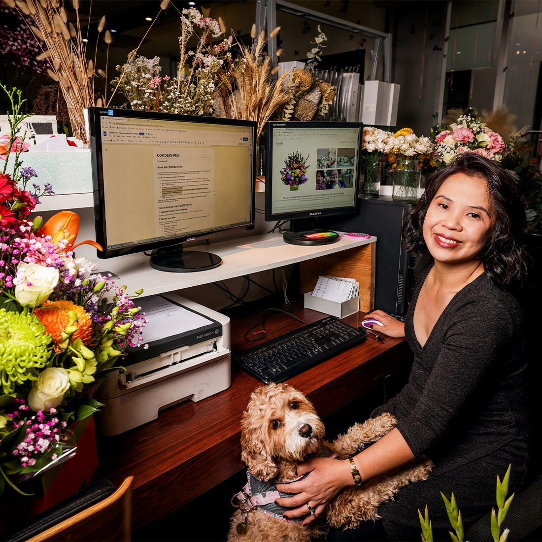 Kellee from Kellee flowers in her flower shop with her puppy