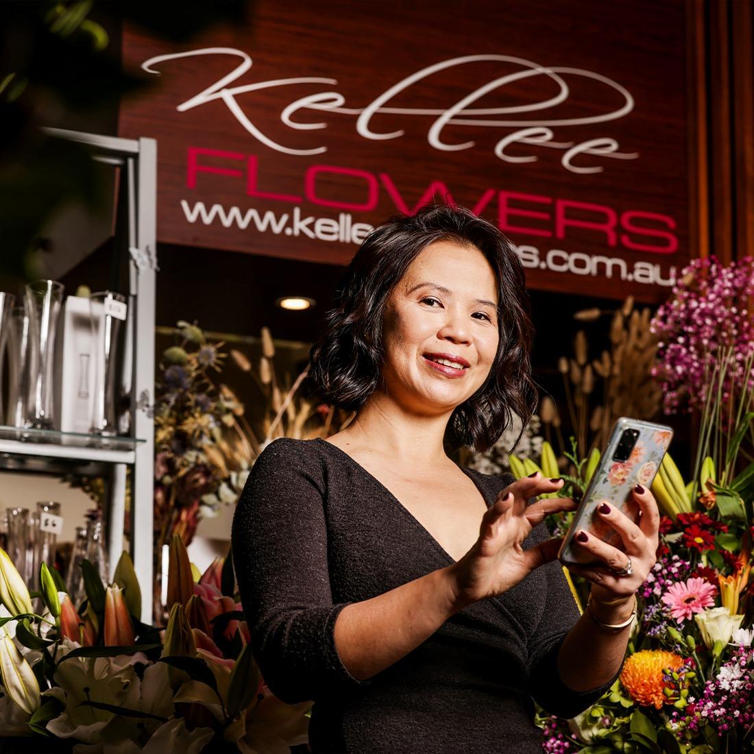 Kellee from Kellee flowers in her flower shop using her mobile