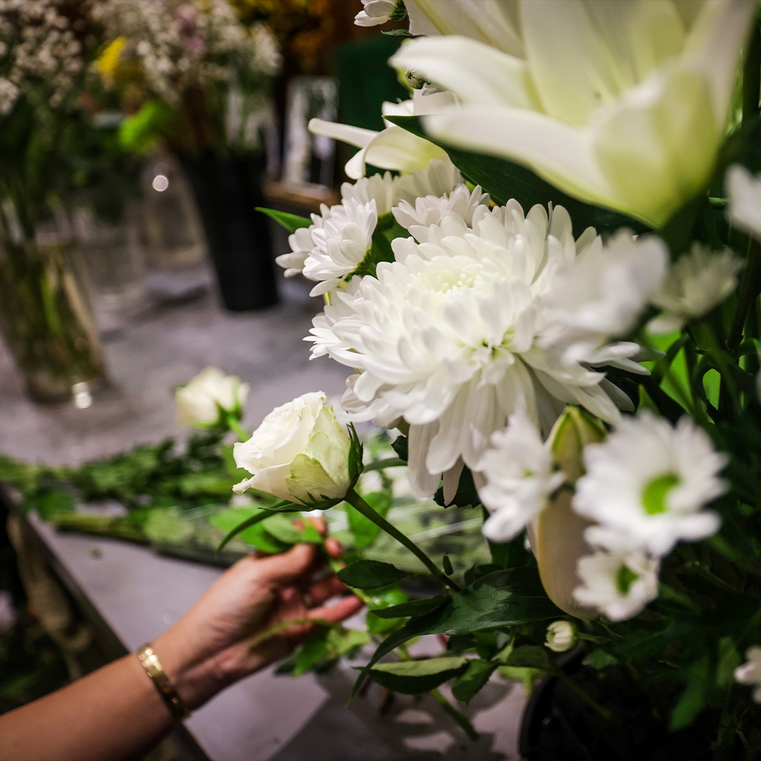 A woman's hand arranging flowers