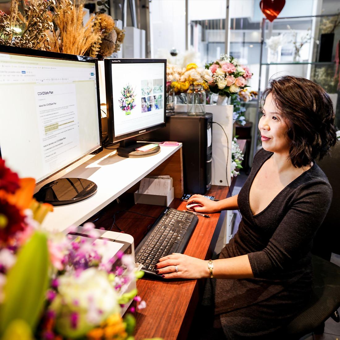 Kellee from Kellee flowers in her flower shop using her computer