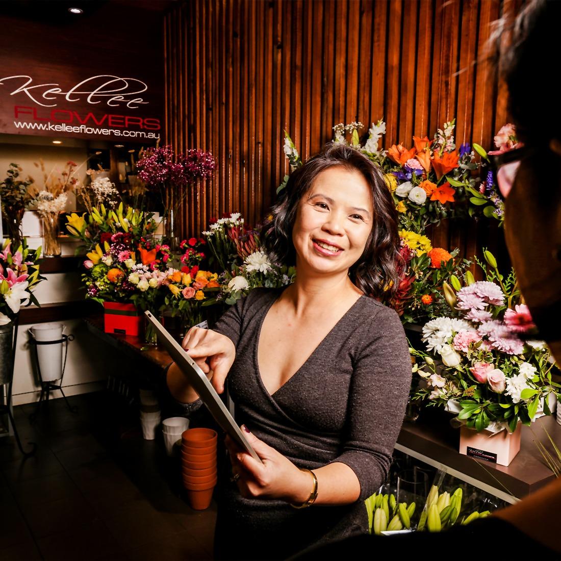 Kellee from Kellee flowers in her flower shop using her tablet, talking to a customer