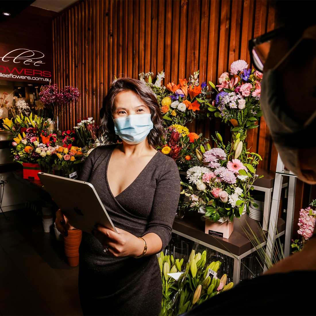 Kellee from Kellee flowers in her flower shop using her tablet, wearing a mask and talking to a customer