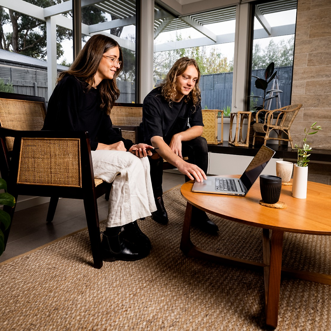 Phoebe and Tom Simpson sitting on a chair with a laptop